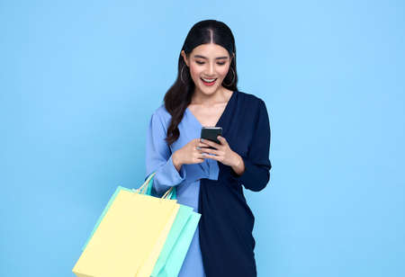 Beautiful young Asian woman carrying bags shopping online with smartphone isolated on blue background. Banco de Imagens