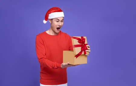 Young asian man in red casual attire wearing Santa hat opening presents box and looking excited and surprise something inside box isolated on purple background.Happy new year concept.