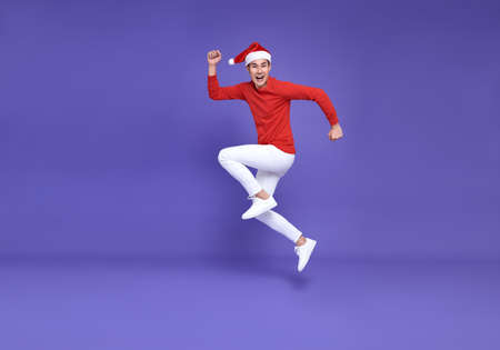 Young asian man in red casual attire wearing Santa hat jumping and smile face on purple background.Happy new year concept.