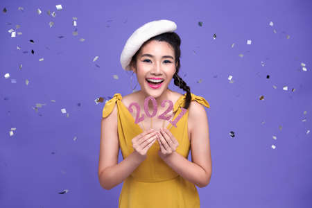 Pretty asian woman smile  welcoming the new year 2021with silver confetti party on bright purple background. Standard-Bild