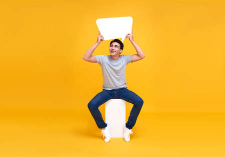 Excited Asian man sitting and holding blank speech bubbles. looking up with smile on yellow background.