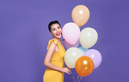 Pretty young asian woman at celebration party holding colourful balloon and smile face. Happy new year or Birthday eve celebrating concept.