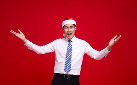 Excited asian business man wearing Santa hat and action open hand gesture  on isolated over red background.Happy new year concept. Standard-Bild