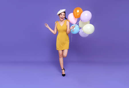 Pretty young asian woman at celebration party holding colourful balloon running and smile face. Happy new year or Birthday eve celebrating concept on bright purple background.