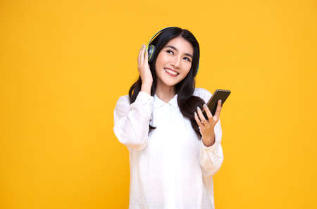 Happy smiling Asian woman wearing wireless headphones listening to music with smartphone on bright yellow background.