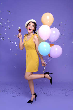 Pretty young asian woman at celebration party holding colourful balloon and wine glass with enjoy with confetti falling everywhere on her. Happy new year or Birthday eve celebrating concept Standard-Bild