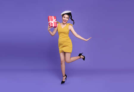 Pretty young asian woman holding red presents with jumping joyfully  .Happy new year or Birthday eve celebrating concept.on bright purple background.