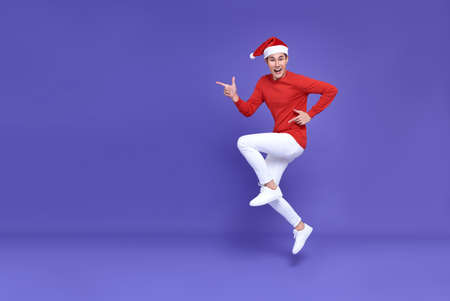 Young asian man in red casual attire wearing Santa hat jumping with pointing finger aside front a copy space and smile face on purple background.Happy new year concept.