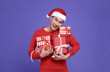 Young asian man in red casual attire wearing Santa hat and holding stack of presents with smile face on purple background.Happy new year concept.