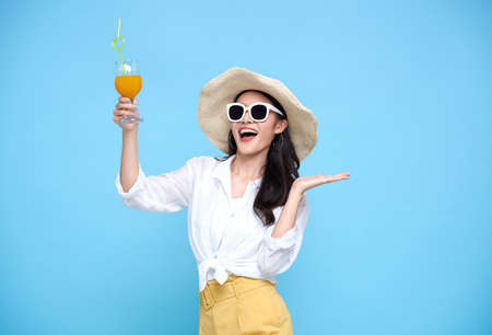 Happy Asian woman in summer casual clothes wearing straw hat, sunglasses holding glass of fresh fruit juice drink isolated on bright blue backgroud.