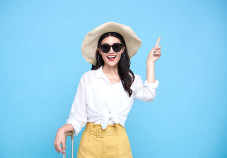 Happy smiling Asian woman dressed in summer clothes and wearing hat with luggage enjoying their summer vacation  and pointing finger a copy space on bright blue background.