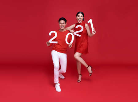 Happy asian couple showing number 2021 greeting happy new year with smiles on bright red background.