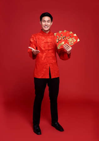 Happy Chinese new year. Asian man holding angpao or red packet monetary gift isolated on red background.