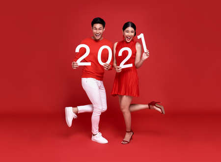 Happy asian couple in red casual attire showing number 2021 greeting happy new year with smiles on bright red background. Stockfoto