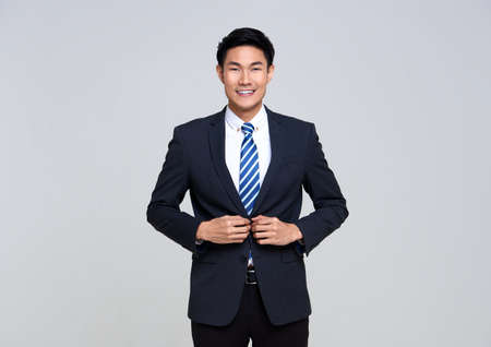 portrait of young Asian businessman smiling confidently while standing isolated on studio white background.