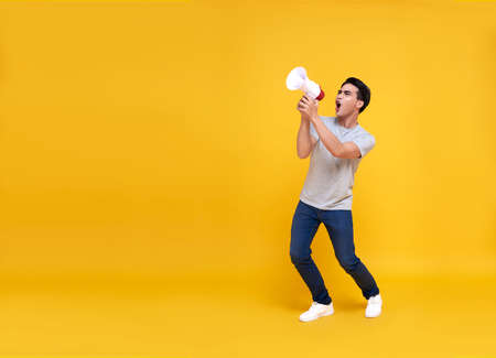 Young Asian man shouting into megaphone making announcement in isolated on yellow background.