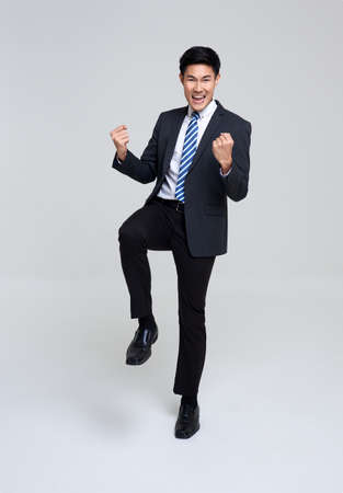 portrait of young Asian businessman happy and success isolated on studio white background. Stockfoto