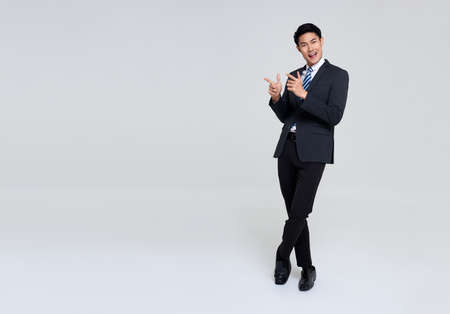 portrait of young Asian businessman hand pointing up to copy space isolated on studio white background.