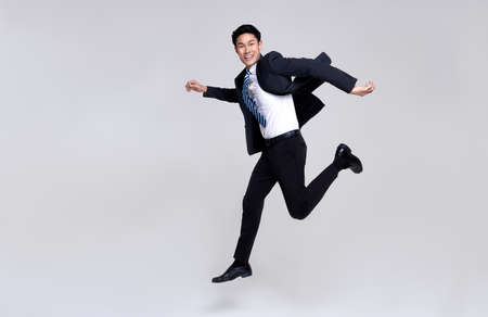 Fun portrait of happy energetic young Asian businessman jumping in mid-air isolated on studio white background.