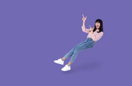 Young beautiful smiling asian girl hand pointing up to copy space isolated on purple background. Stockfoto