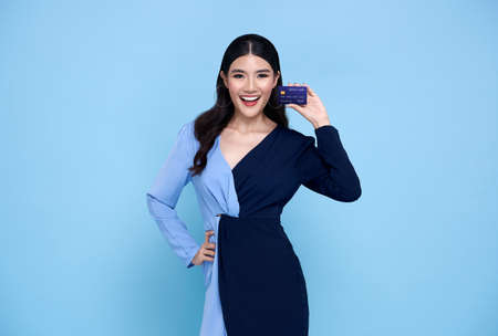 Happy beautiful Asian shopaholic women wearing blue dress showing credit card in hand isolated on blue background. Stockfoto