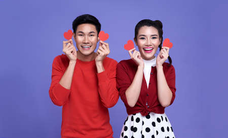 Happy asian couple is holding red paper hearts and smiling isolated on purple background. valentine's day concept.