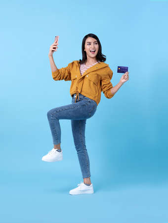 Portrait of a happy young asian woman celebrating with mobile phone and credit card isolated over blue background.