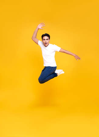Young happy handsome Asian man jumping isolated over yellow background.