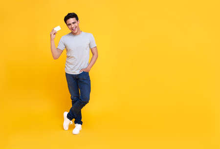 Happy handsome Asian shopaholic man showing credit card in hand isolated on yellow background.