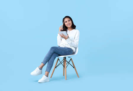 Young woman Asian happy and interested in thinking.While her holding notebook sitting on white chair isolate on bright blue background.