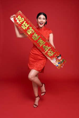 Happy Chinese new year. Asian woman wearing traditional cheongsam qipao dress holding Chinese New Year couplets isolated on red background.