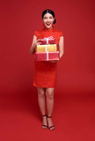 Happy Chinese new year. Asian woman wearing traditional cheongsam qipao dress holding gift box isolated on red background.