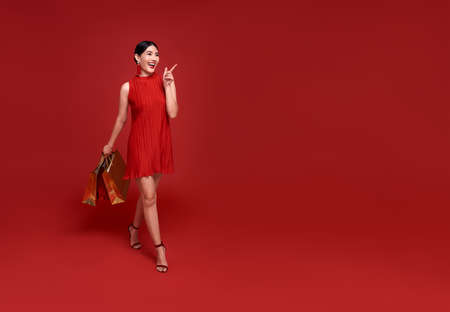 Happy Asian shopaholic woman wearing traditional cheongsam qipao dress hand pointing up to copy space isolated on red background. Happy Chinese new year Stockfoto