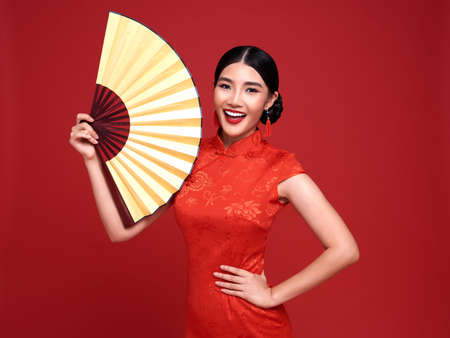 Happy Chinese new year. Asian woman wearing traditional cheongsam qipao dress holding fan isolated on red background.