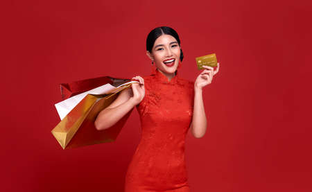 Happy Asian shopaholic woman wearing traditional cheongsam qipao dress holding credit card and shopping bag isolated on red background. Happy Chinese new year