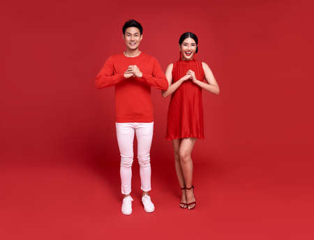 Happy asian couple in red casual attire with gesture of congratulation greeting happy new year 2021 on bright red background. Stockfoto