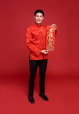 Happy Chinese new year. Asian man holding Chinese New Year couplets isolated on red background.