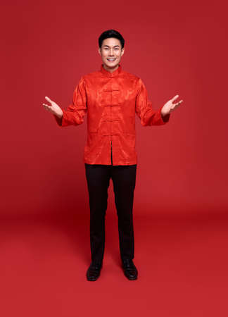 Happy Chinese new year. Handsome Asian man with open hand gesture of introduce isolated on red background.