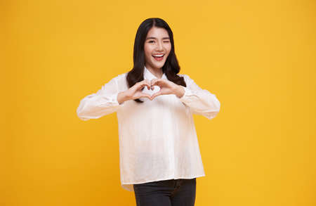 Young beautiful Asian woman showing heart sign isolated on yellow background. love and happy valentine concept.