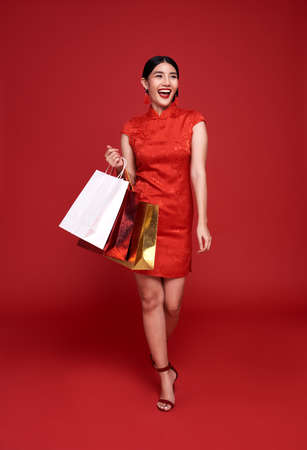 Happy Asian shopaholic woman wearing traditional cheongsam qipao dress holding shopping bag isolated on red background. Happy Chinese new year