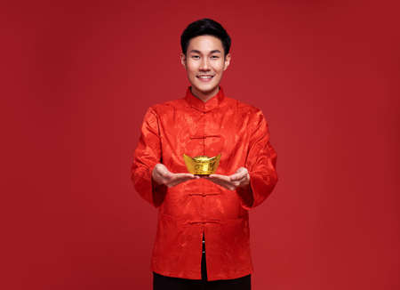 Happy Chinese new year. Asian man wearing in traditional costume holding gold ingot isolated on red background.