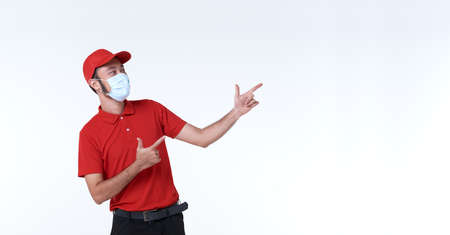 Asian delivery man wearing face mask in red uniform with his finger pointing to copy space isolated over white background. social distancing and new normal concept. Stock fotó