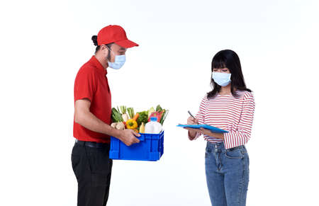Asian delivery man wearing face mask in red uniform with groceries box of food, fruit, vegetable and drink give to woman costumer isolated over white background. social distancing and new normal concept.