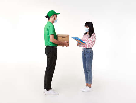 Asian delivery man wearing face mask in green uniform with parcel box give to woman costumer isolated over white background. social distancing and new normal concept. Stock fotó