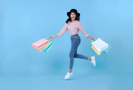 Cheerful happy thai asian woman enjoying shopping,  she is carrying shopping bags and jumping to get the latest offers at the shopping center. Stock fotó