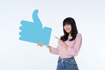 Young happy cheerful asian woman showing thumb up or like sign isolated on white background. Stock fotó