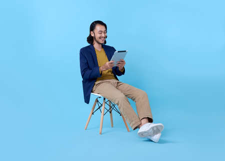 Business man asian happy smiling using a digital tablet while sitting on chair isolated on bright blue background.