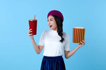 Excited Asian woman watching movie film holding popcorn and cup of soda isolated on bright blue background. Stock fotó