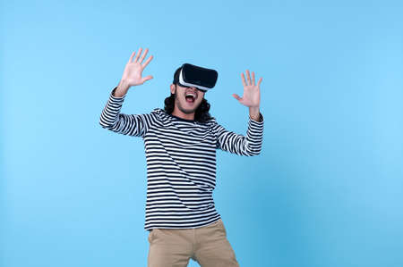 Excited Asian man wearing virtual reality goggles watching movies on blue background. Stock fotó