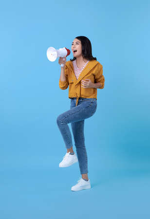 Young Asian woman shouting into megaphone making announcement in isolated on blue background. Stock fotó